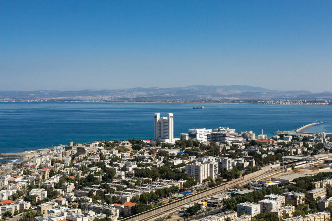 Blick auf die Hafeneinfahrt von Haifa, im Vordergrund ein Wohnviertel, im Hintergrund die hügelige Küstenlandschaft