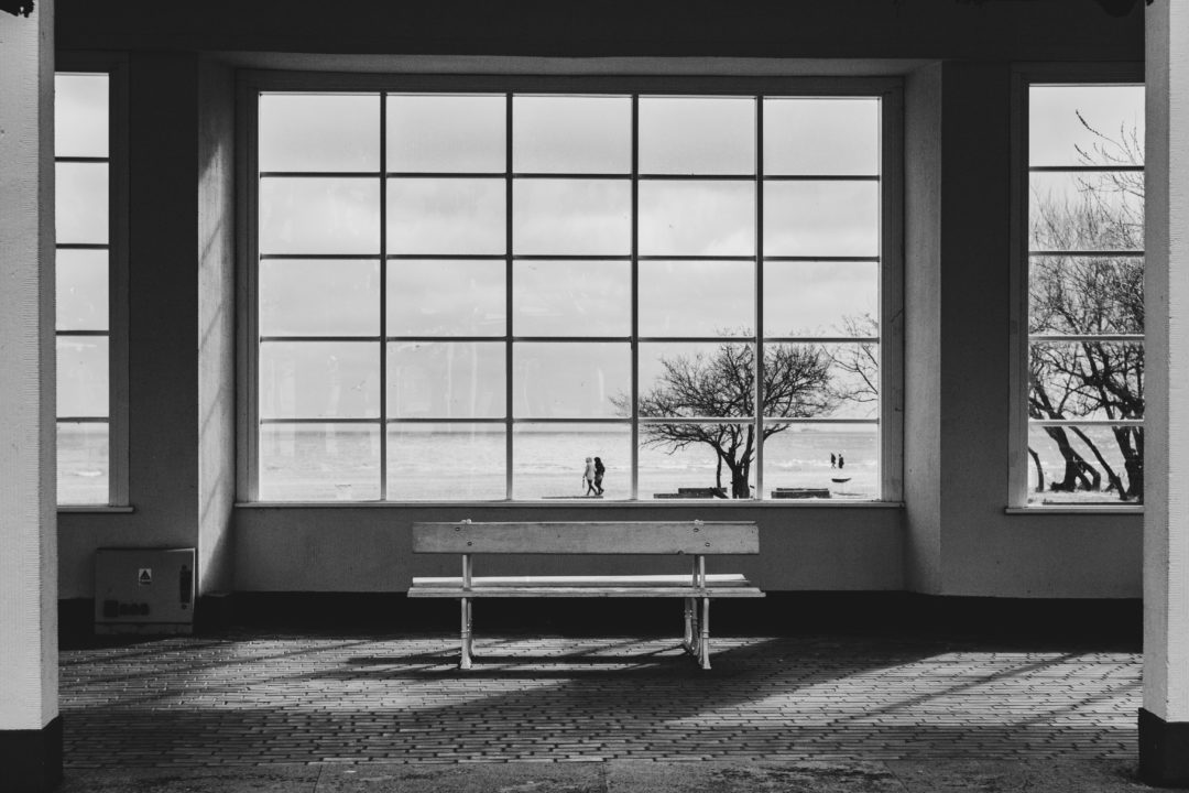 Eine Bank steht in einem Rundgang, dahinter ein großes Fenster mit Sicht auf Menschen am Strand
