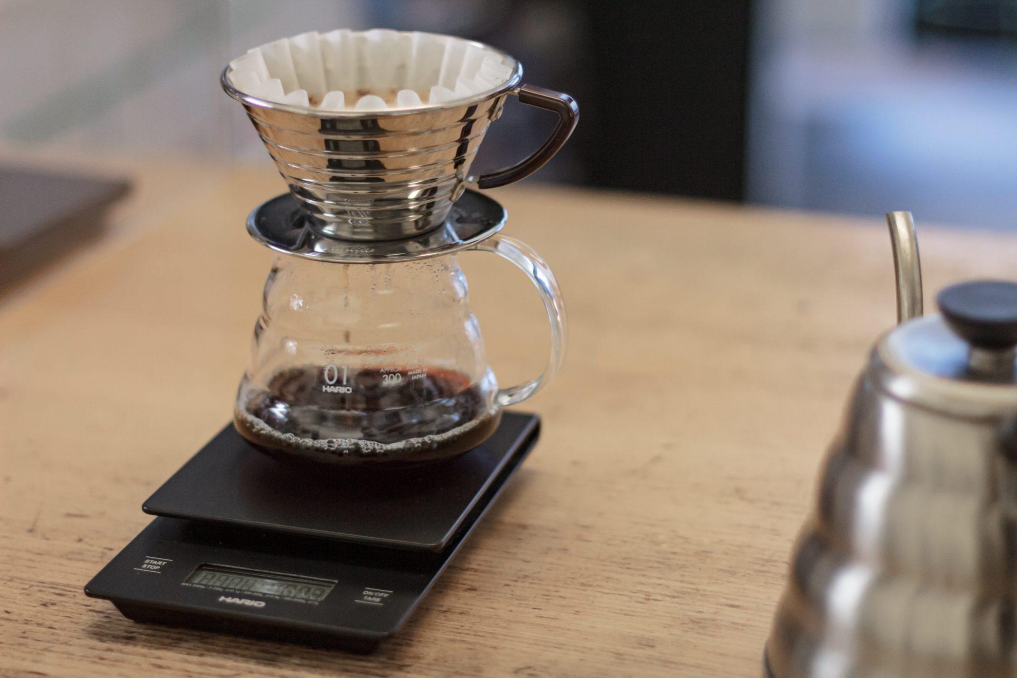 Eine Glaskanne mit Metall-Filter steht auf einer schwarzen Waage, der Kaffee tropft durch den Filter in die Kanne