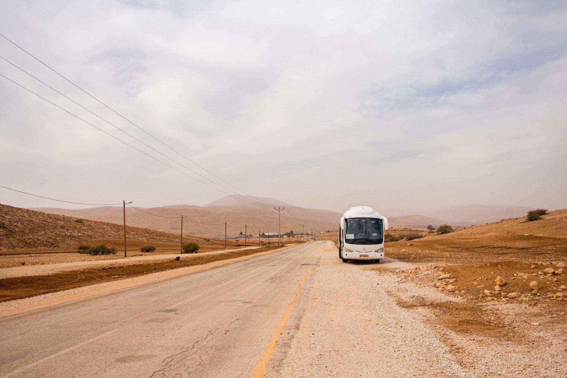 An einer staubigen kleinen Asphaltstraße steht ein weißer Bus, links verlaufen Strommasten, im Hintergrund ist eine hügelige Wüstenlandschaft zu sehen