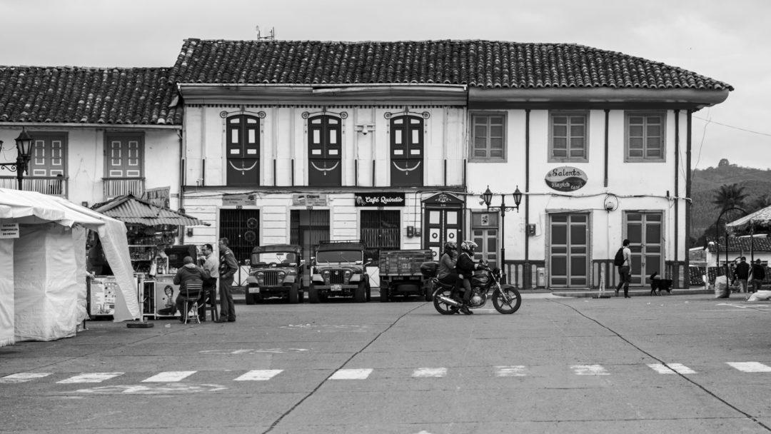 Zwei Menschen auf einem Motorrad fahren über einen Platz in Salento in Kolumbien.