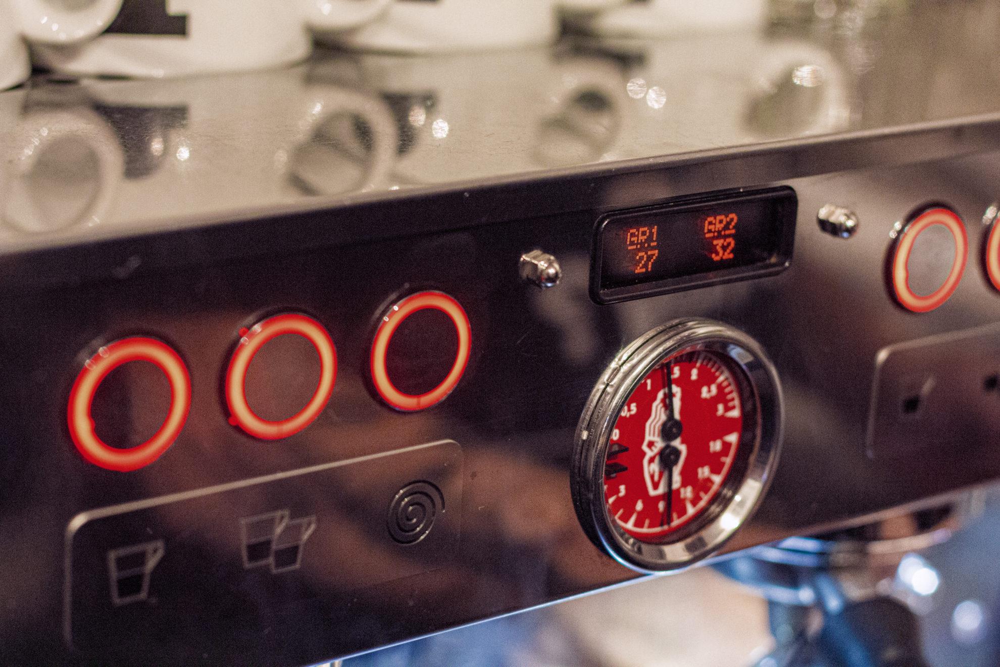 Nahaufnahme einer Espressomaschine mit Manometer und digitaler Anzeige.
