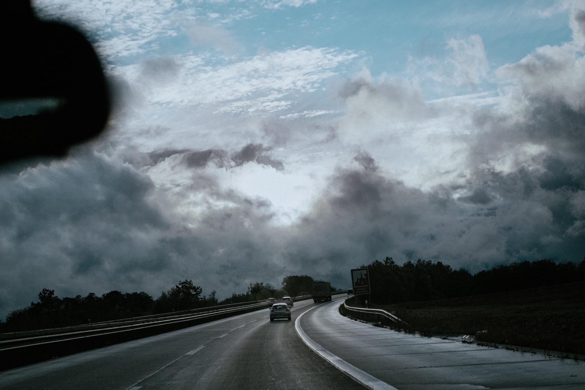 Blick aus der Frontscheibe eines Autos auf die Autobahn den Berg hinauf. Über der Autobahn bricht die Sonne durch die Wolken.