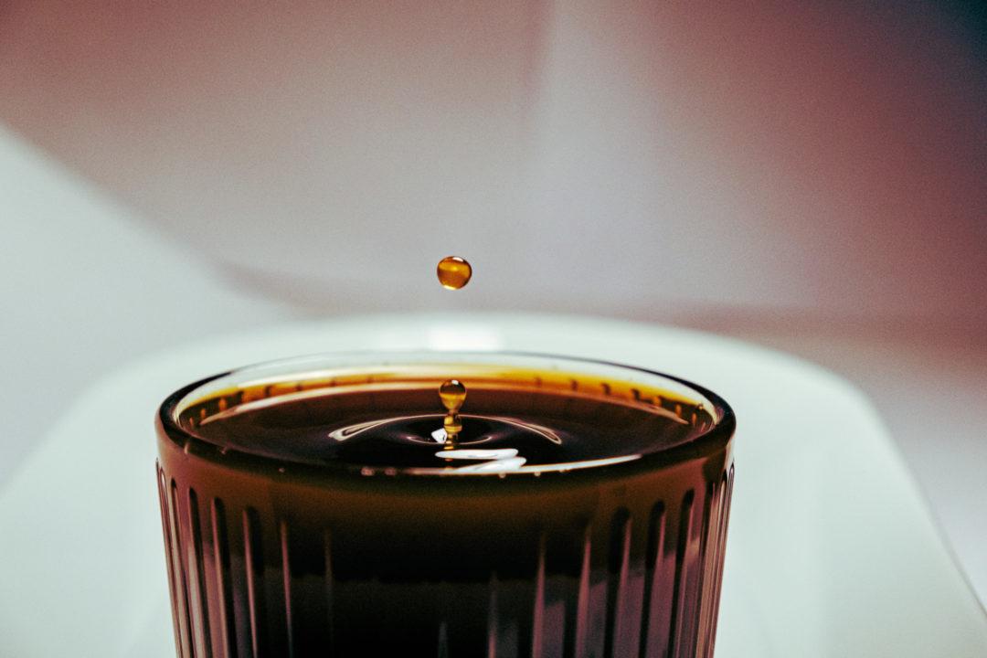 Ein einzelner Tropfen Kaffee fällt in ein Glas gefüllt mit Filterkaffee.