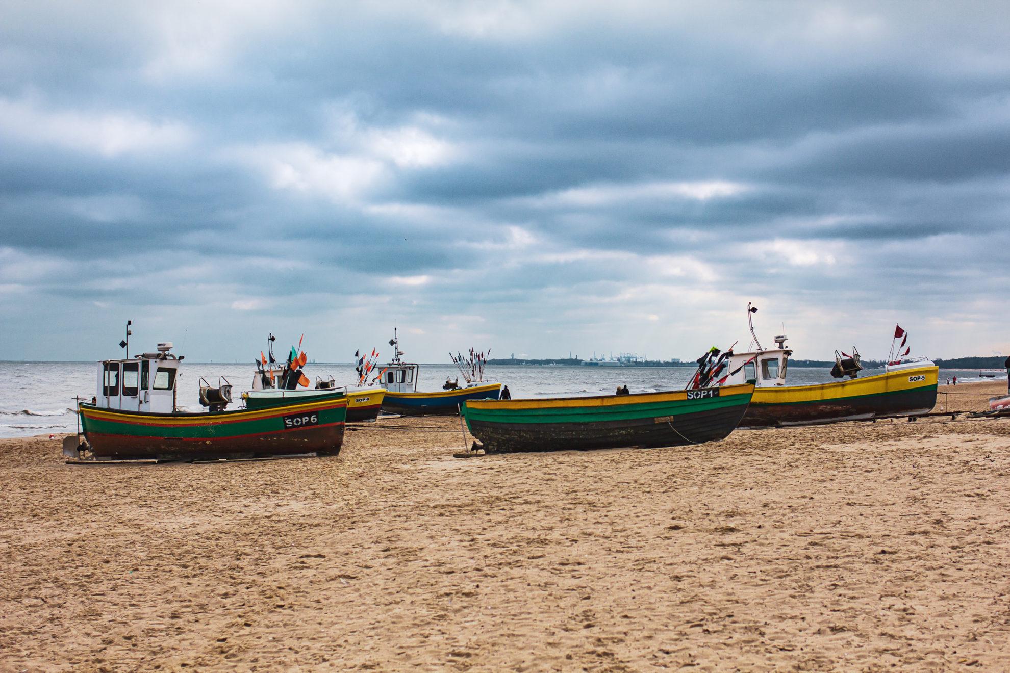 Mehrere kleine bunte Fischerboote liegen am Strand, über ihnen stehen dunkle Wolken.