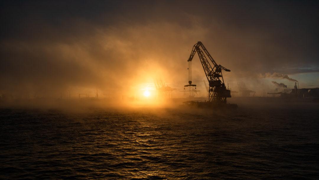 Im hellen Gegenlicht der Sonne schwimmt ein Schwimmkran über die Elbe durch feine Nebelschwaden.