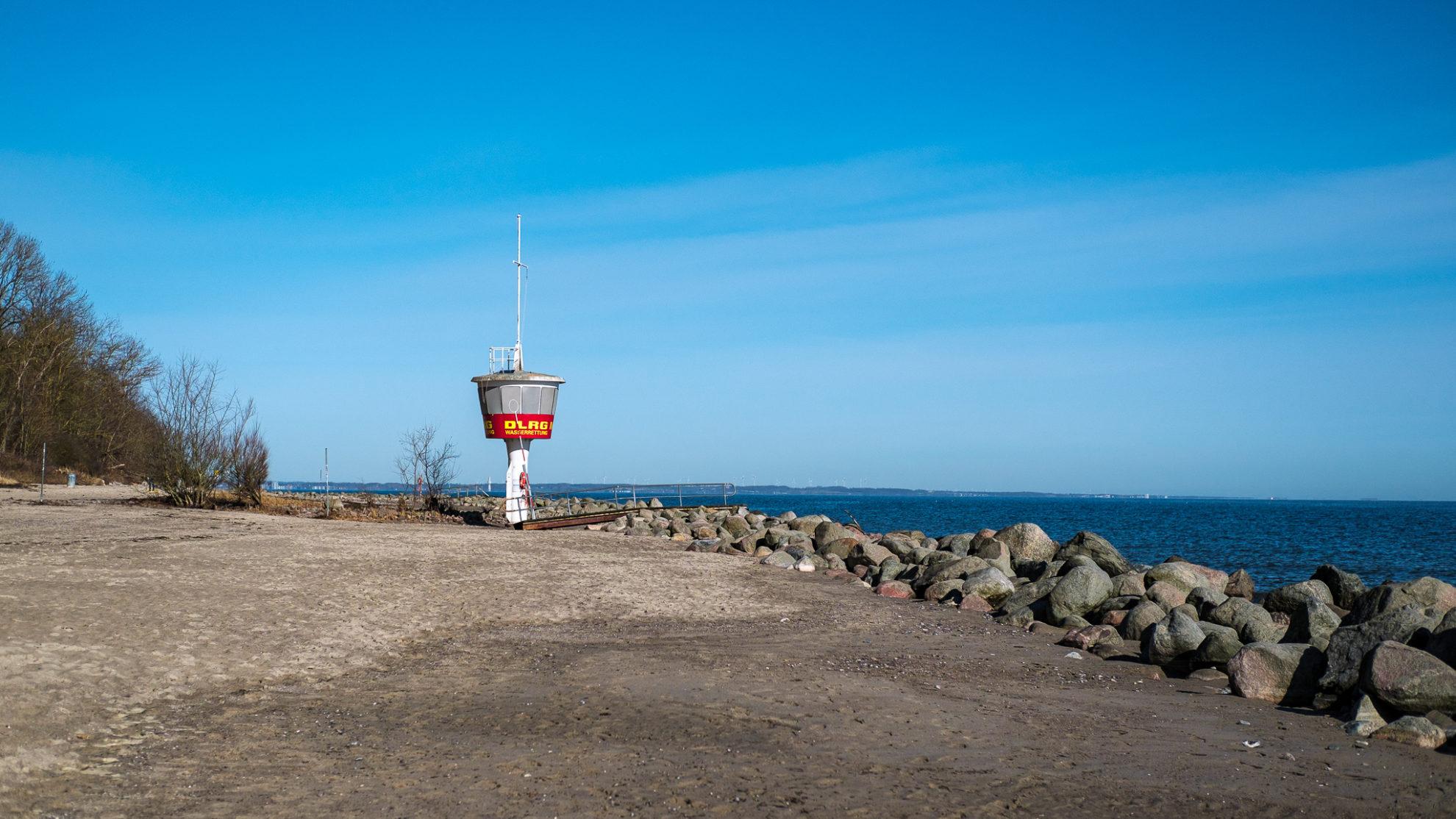 Ein Turm der DLRG mit weißem Fuß steht am Strand. Große Steine grenzen den Sandstrand vom Wasser ab. Der Himmel ist strahlend blau.