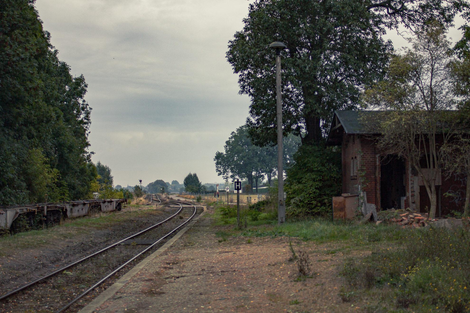 Blick über den ehemaligen Bahnsteig. Auf dem linken Gleis stehen abgestellte Waggons. Auf der rechten Seite liegen einige Ziegel vor einem heruntergekommenen Schuppen. Der Himmel ist grau, die Stimmung ist gedrückt.