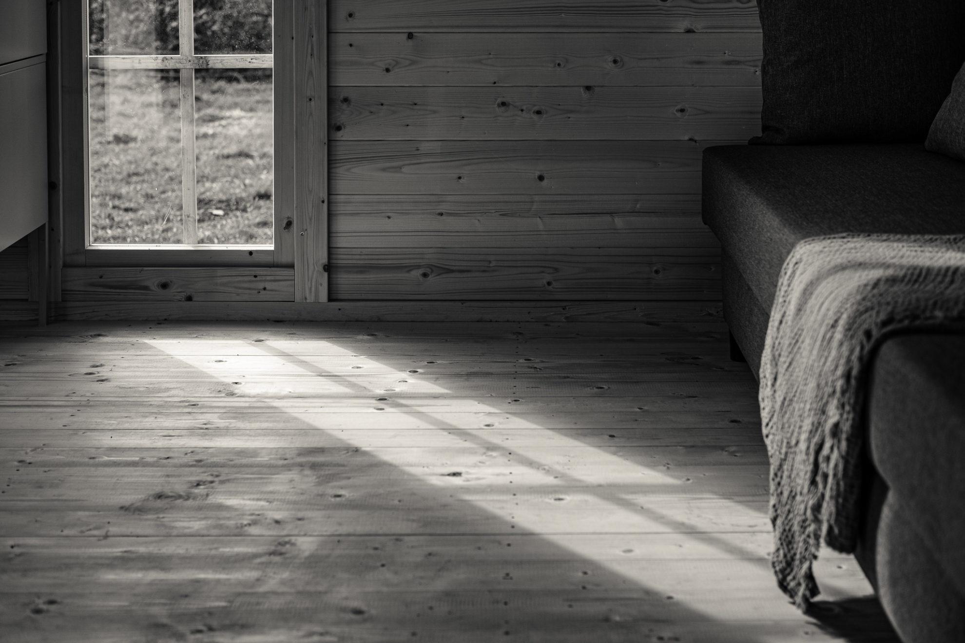 Sonnenstrahlen bilden das Fenster auf dem Holzboden ab. Der Holzboden zeigt im Schattenspiel seine raue Struktur. Im rechten Teil des Bildes fallen die Sonnenstrahlen auf eine Decke, die von einem Sofa herunterhängt.