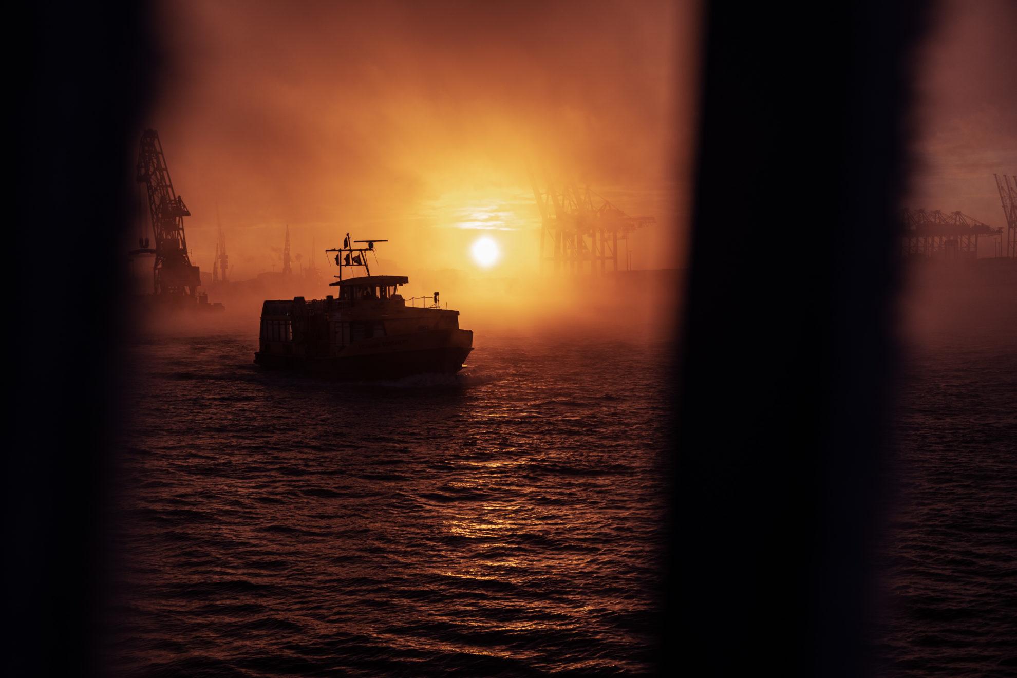 Im Gegenlicht der aufgehenden Sonne fährt eine Hafenfähre über die Elbe