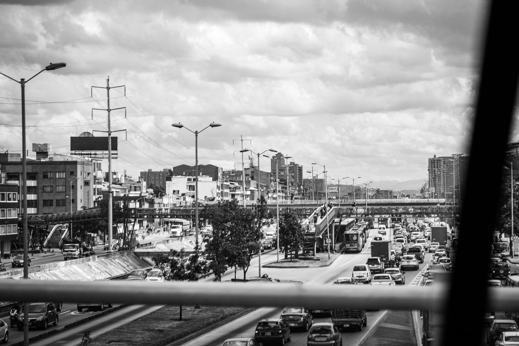 Blick aus einem Auto von einer Brücke auf eine verstopfte mehrspurige Straße in Bogota.