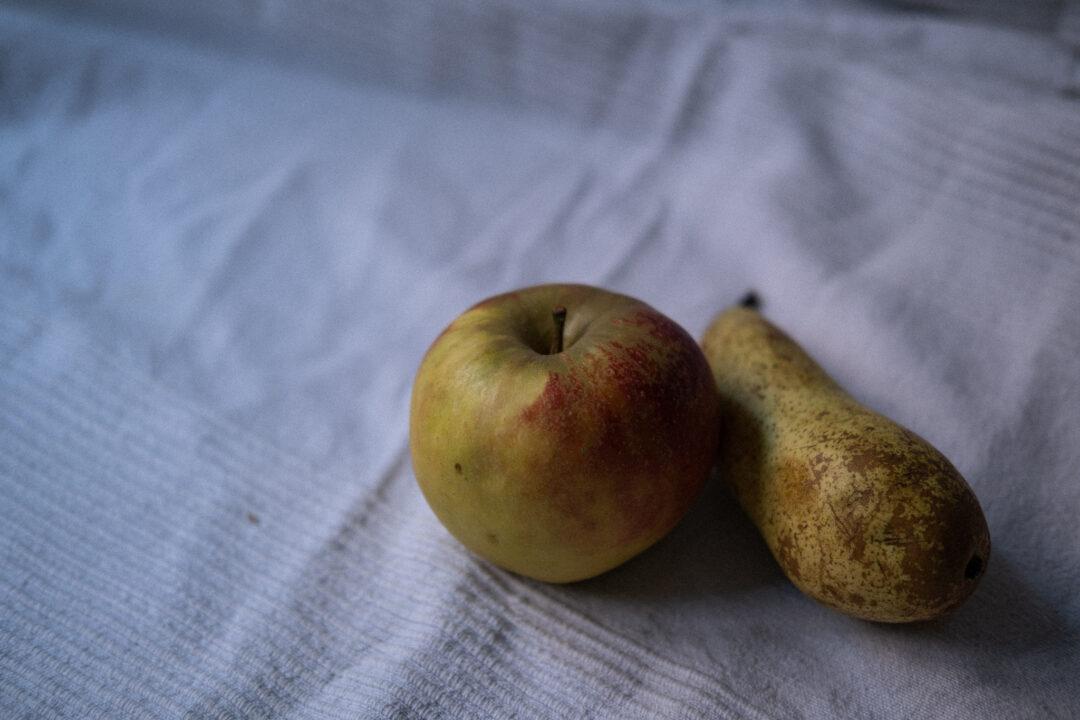 Ein rot gefleckter Apfel und eine lange schmale Birne liegen auf einem weißen Tuch und bilden ein Stillleben