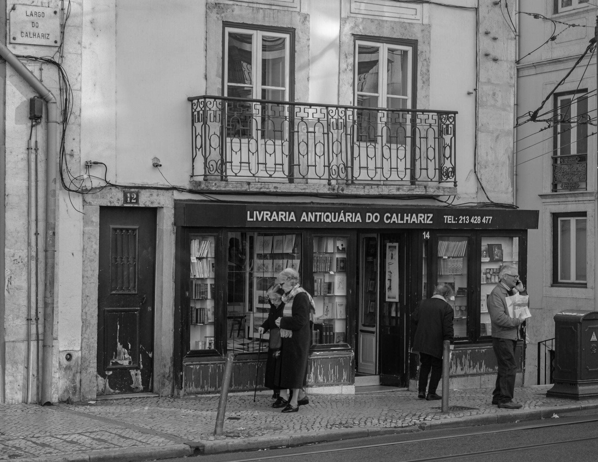 Eine Szene mit einigen älteren Menschen vor einer Antiquitäten-Buchhandlung in der Altstadt von Lissabon.