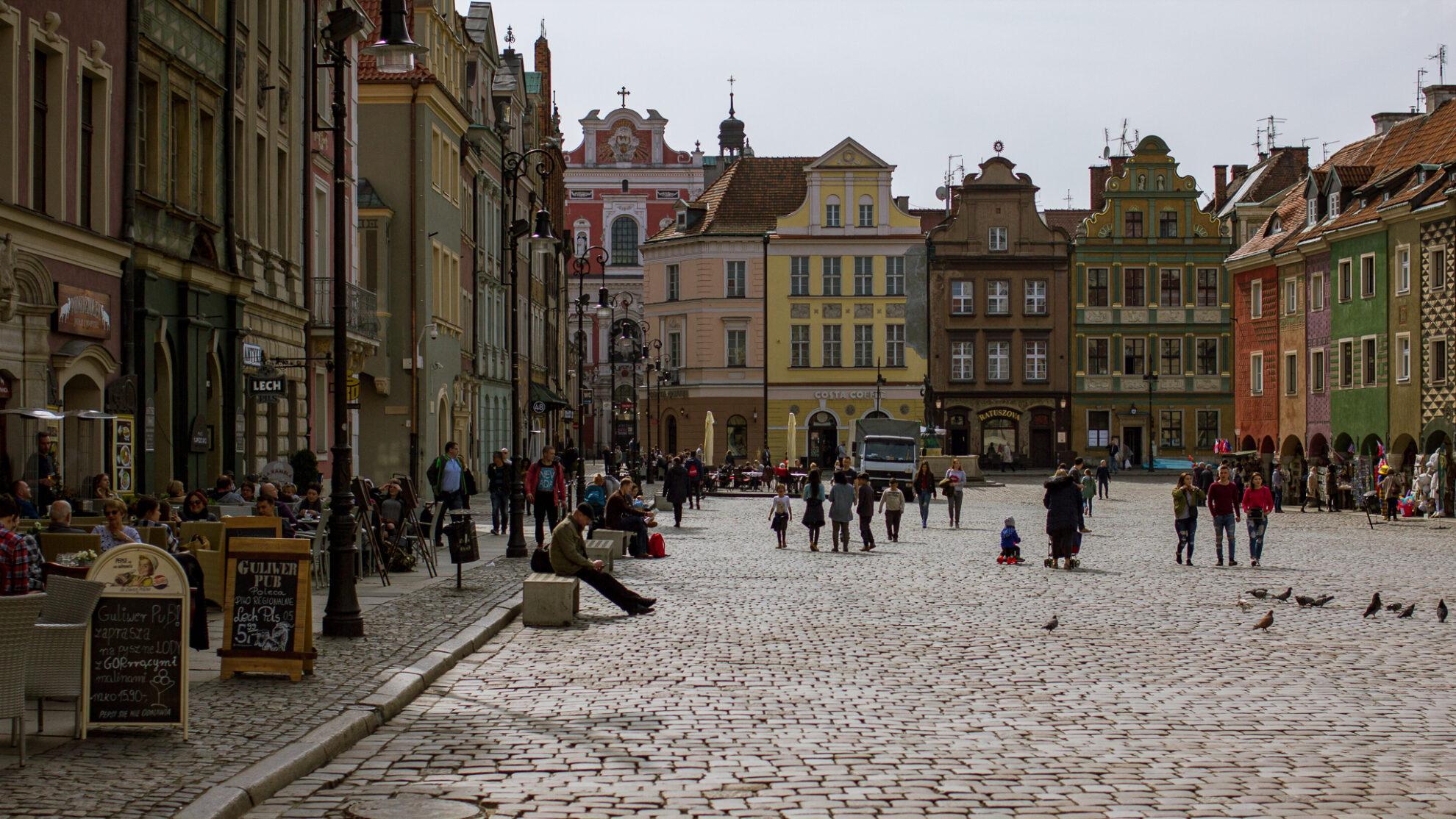 Blick auf den gepflasterten Marktplatz von Posen, rechts und links gesäumt von bunten, historischen Gebäuden.