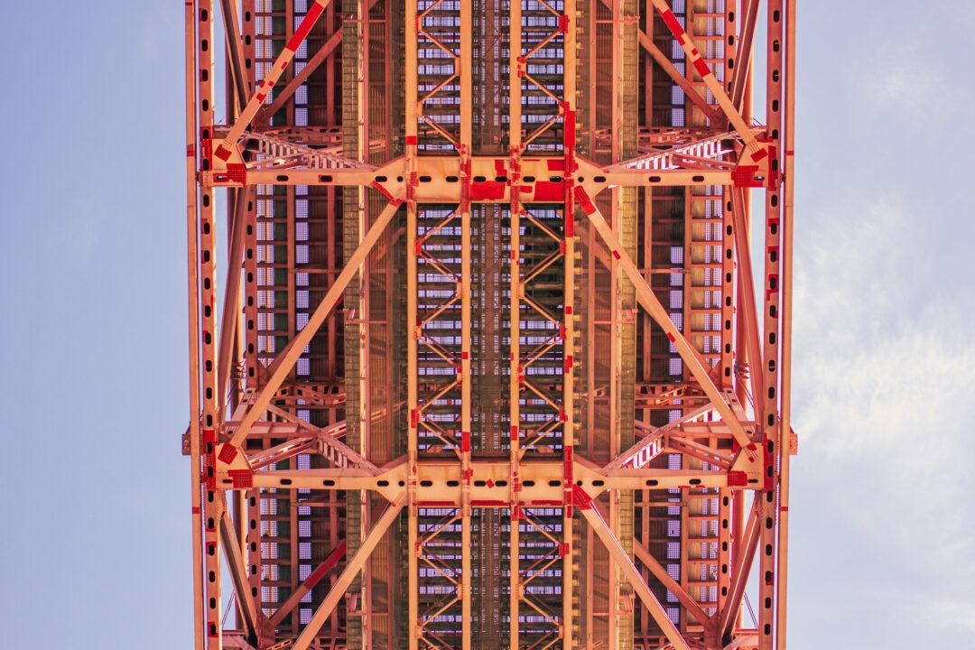 Rote Stahlkonstruktion einer Hängebrücke von unten fotografiert.